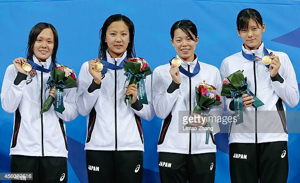 Gold medalist Shiho Sakai Watanabe Kanako Natsumi Hoshi and Miki Uchida of Japan celebrates during the medal ceremony after the swimming Women's 4 x...