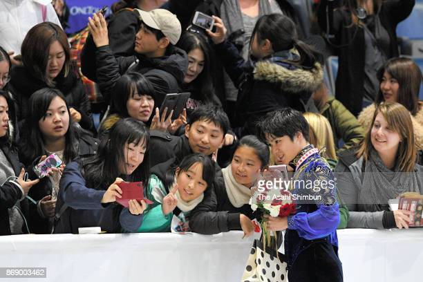 Gold medalist Shoma Uno of Japan poses for photographs with fans after the medal ceremony for the Men's Singles during day two of the ISU Grand Prix...