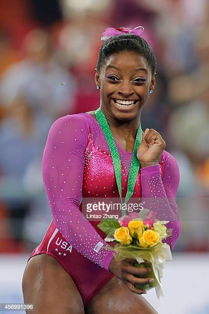 Gold medalist Simone Biles of United States is surprised by a bee during the medal ceremony after the Women's AllAround Final in day four of the 45th...