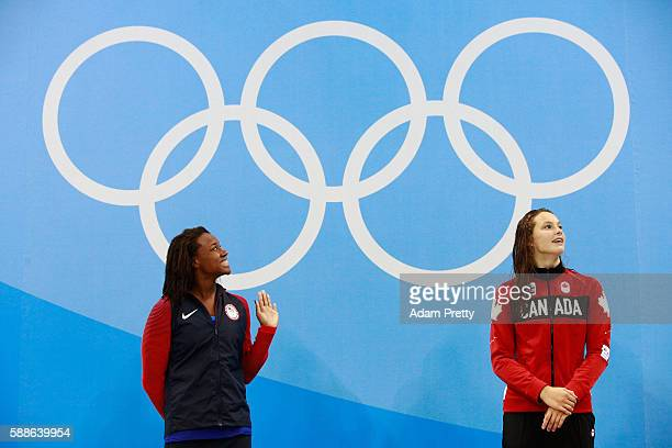 Gold medalist Simone Manuel of the United States and gold medalist Penny Oleksiak of Canada celebrate on the podium during the medal ceremony for the...