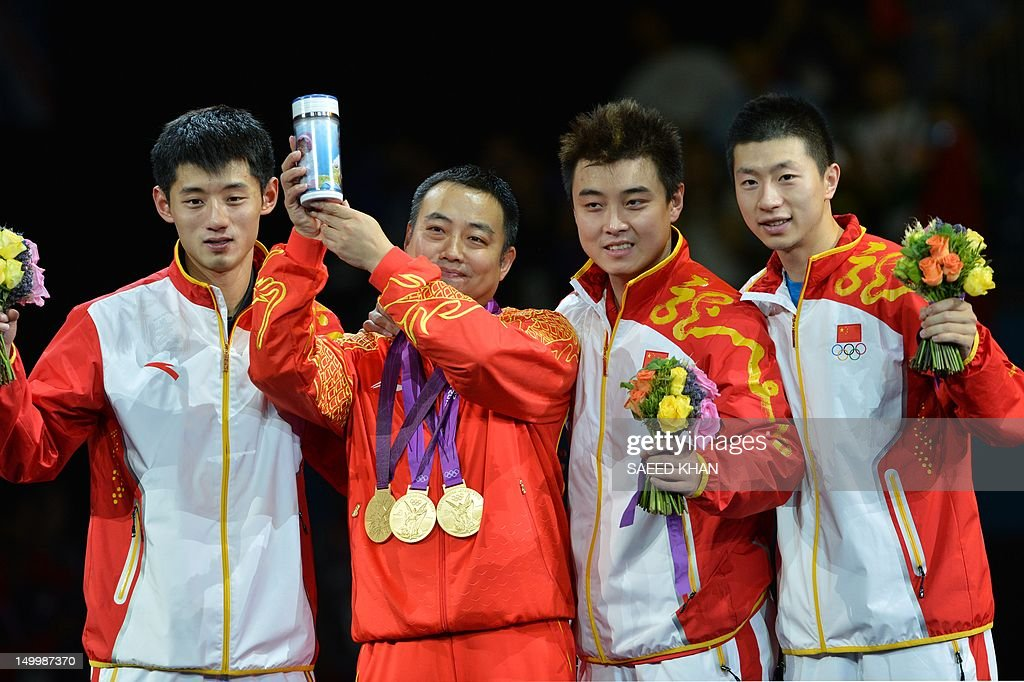 Gold medalist Team China Zhang Jike, coach Liu Guoliang, Wang Hao and Ma Long pose after the podium of the table tennis men's team at the London Olympic games on August 8, 2012 at the Excel arena in London. China completed a clean sweep of all four table tennis gold medals when they beat South Korea 3-0 in the men's team final. AFP PHOTO / SAEED KHAN