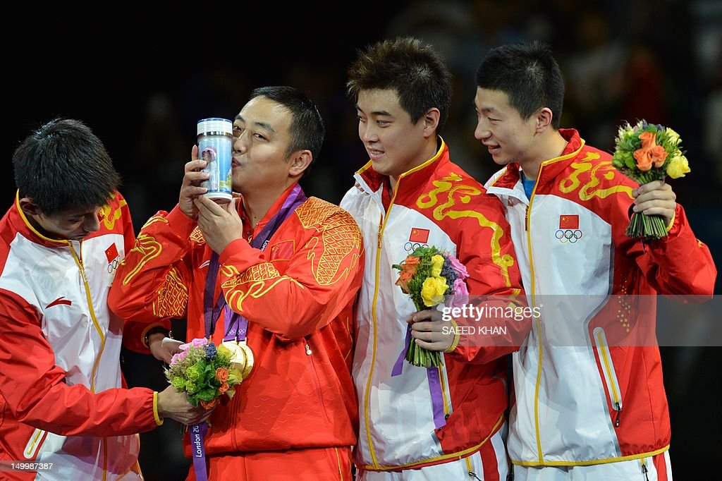 Gold medalist Team China Zhang Jike, coach Liu Guoliang, Wang Hao and Ma Long pose after the podium of the table tennis men's team at the London Olympic games on August 8, 2012 at the Excel arena in London. China completed a clean sweep of all four table tennis gold medals when they beat South Korea 3-0 in the men's team final.