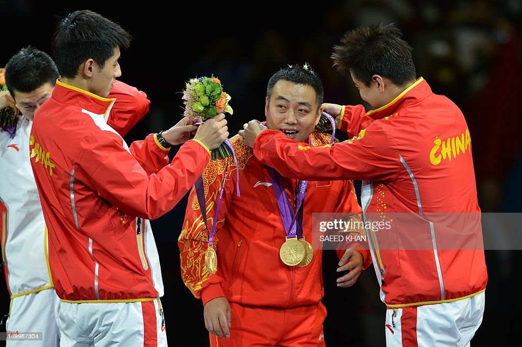Gold medalist Team China Zhang Jike, Wang Hao and Ma Long give their medals to coach Liu Guoliang (2D-R) after the podium of the table tennis men's team at the London Olympic games on August 8, 2012 at the Excel arena in London. China completed a clean sweep of all four table tennis gold medals when they beat South Korea 3-0 in the men's team final. AFP PHOTO / SAEED KHAN