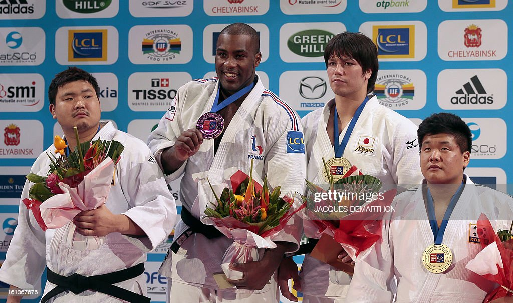 Gold medalist Teddy Riner from France (2ndL) poses on the podium flanked by South Korea's Kim Sung-Min (L), silver medalist, Japan's Sichinohe Ryu (2ndR) and South Korea's Cho Guham, bronze medalists, on February 10, 2013, after winning the Men +100kg final of the Paris International Judo tournament, part of the Grand Slam, at the Palais Omnisports de Paris-Bercy (POPB) in Paris. AFP PHOTO/JACQUES DEMARTHON