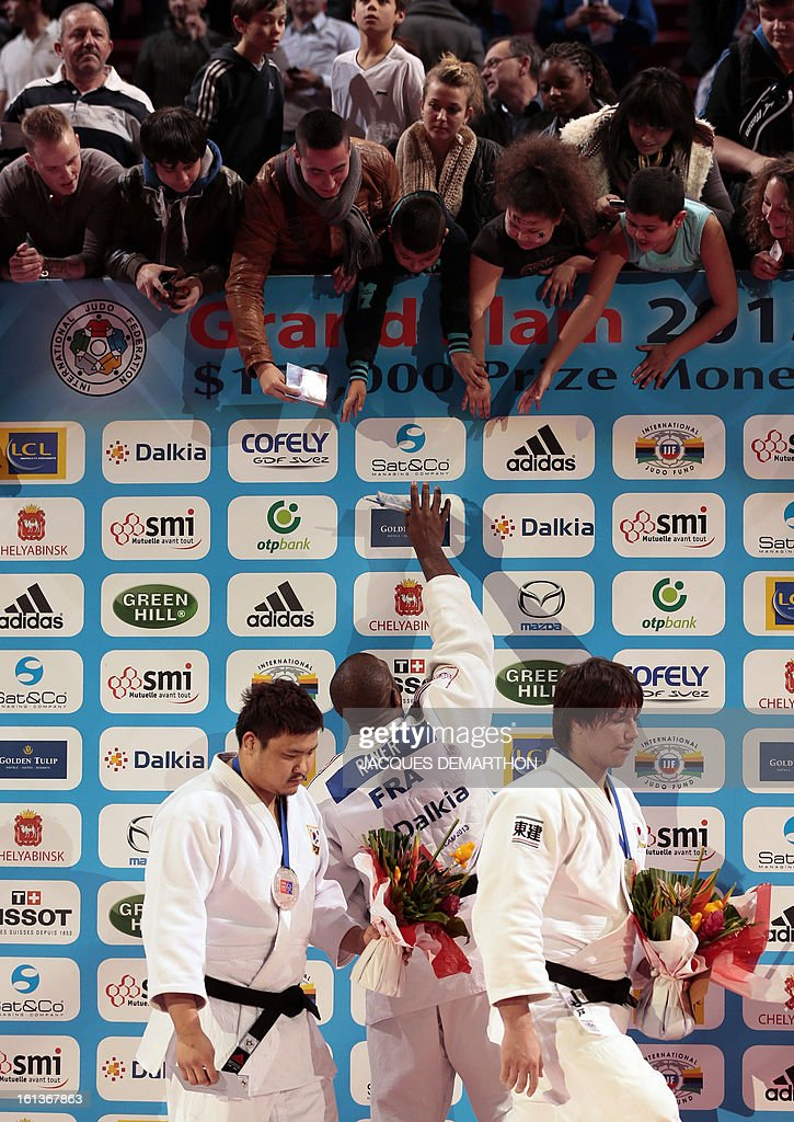 Gold medalist Teddy Riner from France (C) signs autographs on the podium after beating South Korea's Kim Sung-Min (L) on February 10, 2013, during the Men +100kg final of the Paris International Judo tournament, part of the Grand Slam, at the Palais Omnisports de Paris-Bercy (POPB) in Paris. AFP PHOTO/JACQUES DEMARTHON