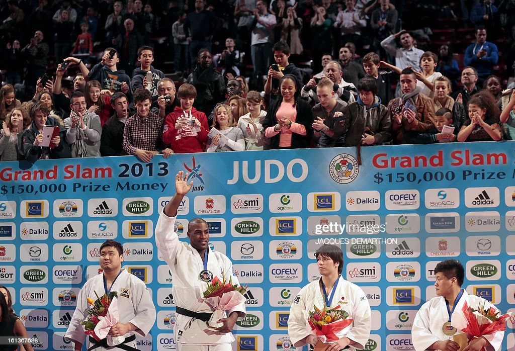 Gold medalist Teddy Riner from France (2ndL) waves on the podium flanked by South Korea's Kim Sung-Min (L), silver medalist, Japan's Sichinohe Ryu (2ndR) and South Korea's Cho Guham, bronze medalists, on February 10, 2013, after winning the Men +100kg final of the Paris International Judo tournament, part of the Grand Slam, at the Palais Omnisports de Paris-Bercy (POPB) in Paris. AFP PHOTO/JACQUES DEMARTHON