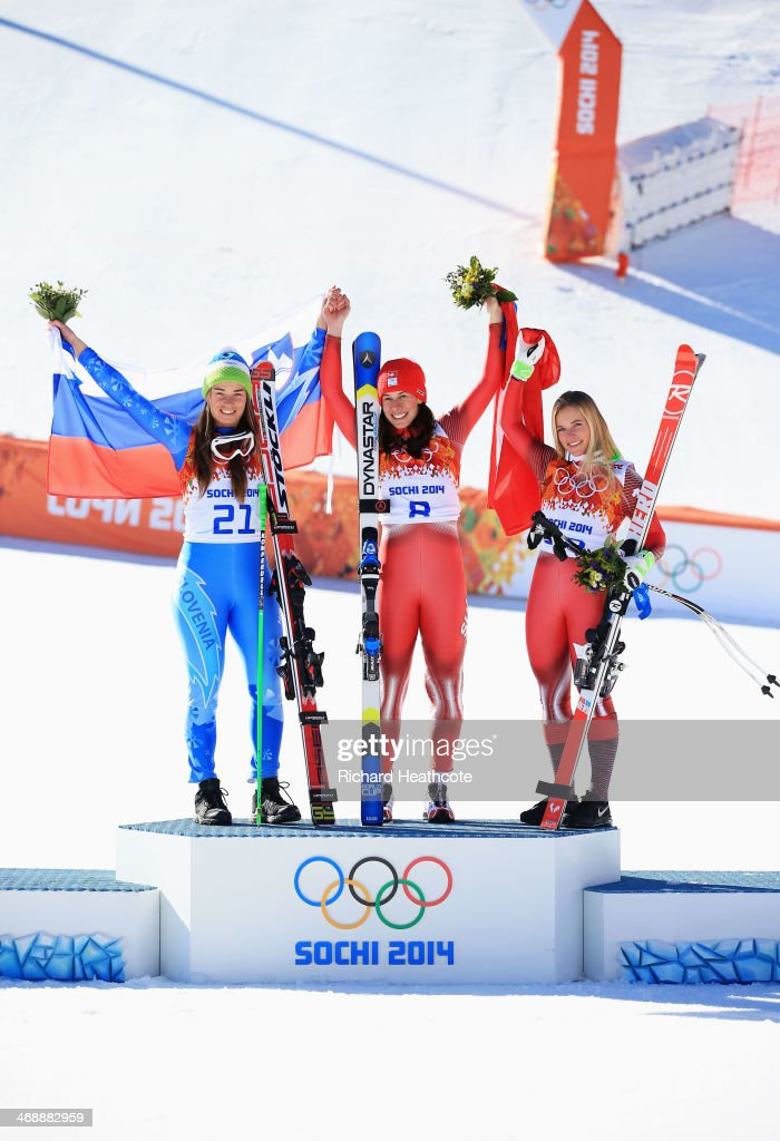 Gold medalist <a gi-track='captionPersonalityLinkClicked' href=/galleries/search?phrase=Tina+Maze&family=editorial&specificpeople=213514 ng-click='$event.stopPropagation()'>Tina Maze</a> of Slovenia, gold medalist <a gi-track='captionPersonalityLinkClicked' href=/galleries/search?phrase=Dominique+Gisin&family=editorial&specificpeople=4083154 ng-click='$event.stopPropagation()'>Dominique Gisin</a> of Switzerland and bronze medalist <a gi-track='captionPersonalityLinkClicked' href=/galleries/search?phrase=Lara+Gut&family=editorial&specificpeople=4860592 ng-click='$event.stopPropagation()'>Lara Gut</a> of Switzerland celebrate on the podium during the flower ceremony for during the Alpine Skiing Women's Downhill on day 5 of the Sochi 2014 Winter Olympics at Rosa Khutor Alpine Center on February 12, 2014 in Sochi, Russia.