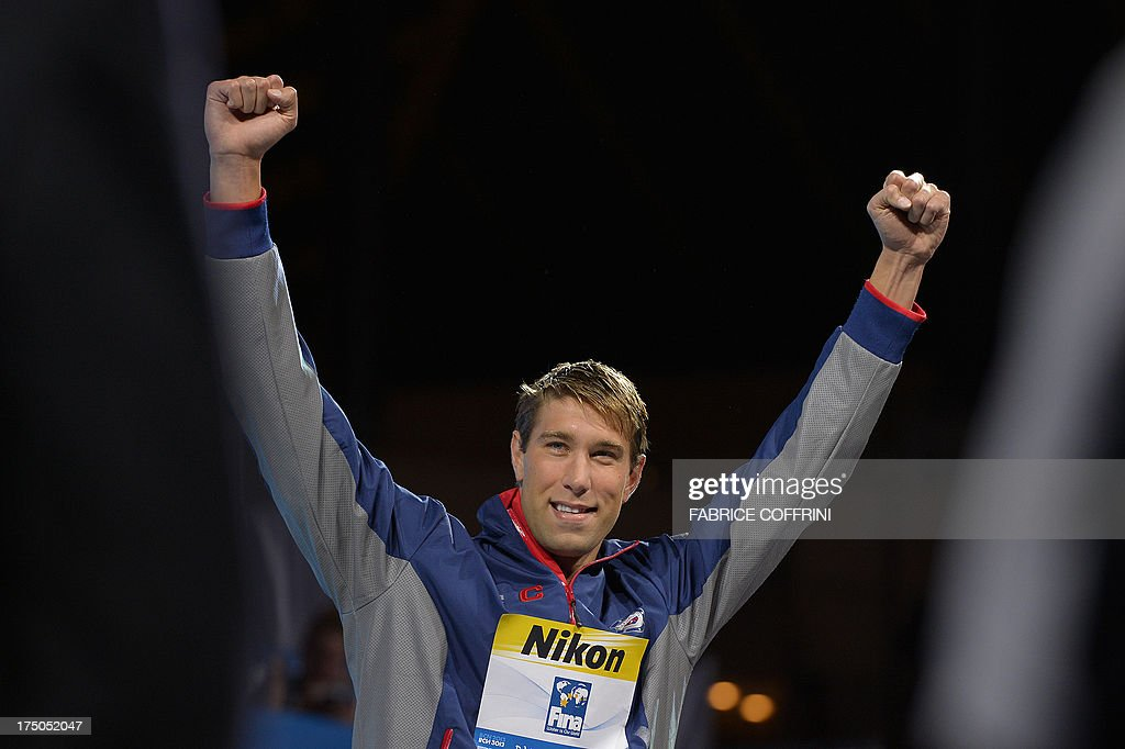 Gold medalist US swimmer Matt Grevers celebrates on the podium during the award ceremony of the men's 100-metre backstroke swimming event in the FINA World Championships at Palau Sant Jordi in Barcelona on July 30, 2013. AFP PHOTO / FABRICE COFFRINI
