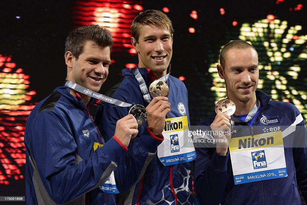 Gold medalist US swimmer Matt Grevers (C), silver medalist US swimmer David Plummer (L) and bronze medalist France's Jeremy Stravius pose on the podium during the award ceremony of the men's 100-metre backstroke swimming event in the FINA World Championships at Palau Sant Jordi in Barcelona on July 30, 2013.