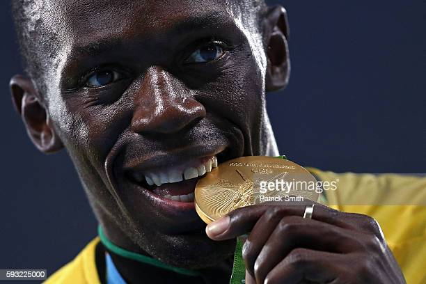 Gold medalist Usain Bolt of Jamaica bites his gold medal during the medal ceremony for the Men's 4 x 100 meter Relay on Day 15 of the Rio 2016...