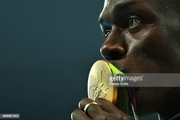 Gold medalist Usain Bolt of Jamaica kisses his gold medal on the podium during the medal ceremony for the Mens 100 metres on Day 10 of the Rio 2016...