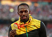 Gold medalist Usain Bolt of Jamaica poses on the podium during the medal ceremony for the Men's 100 metres final during day three of the 15th IAAF...