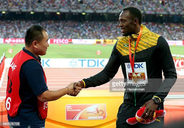 Gold medalist Usain Bolt of Jamaica shakes hands with Tao Song of CCTV the segway driver who accidentally collided with him following the Men's 200...