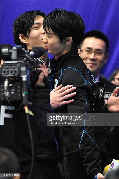 Gold medalist Yuzuru Hanyu is embraced by bronze medalist Keiji Tanaka of Japan prior to the medal ceremony for the Men's Singles during day two of...