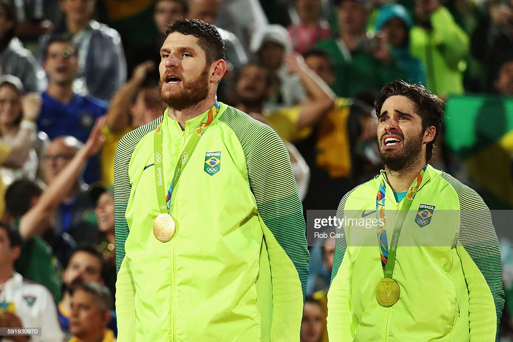 Gold medalists Alison Cerutti and Bruno Schmidt Oscar of Brazil sing their national anthem on the podium during the medal ceremony for the Men's...