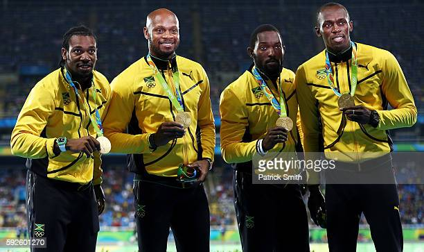 Gold medalists Asafa Powell Yohan Blake Nickel Ashmeade and Usain Bolt of Jamaica stand on the podium during the medal ceremony for the Men's 4 x 100...