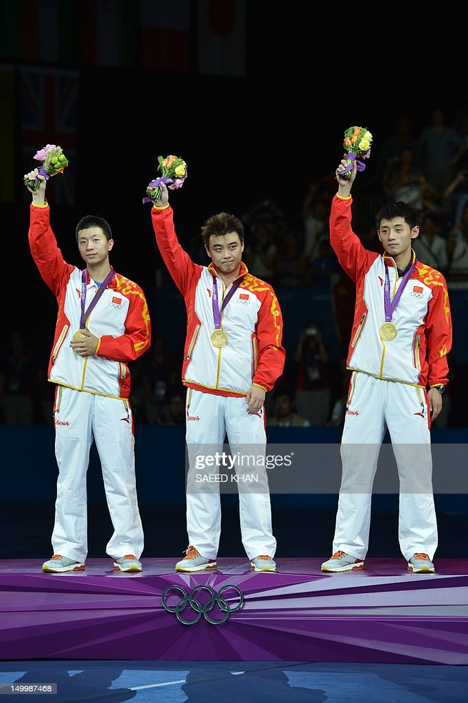 Gold medalists China's Zhang Jike, Wang Hao and Ma Long celebrate on the podium of the table tennis men's team at the London Olympic games on August 8, 2012 at the Excel arena in London. China completed a clean sweep of all four table tennis gold medals when they beat South Korea 3-0 in the men's team final.