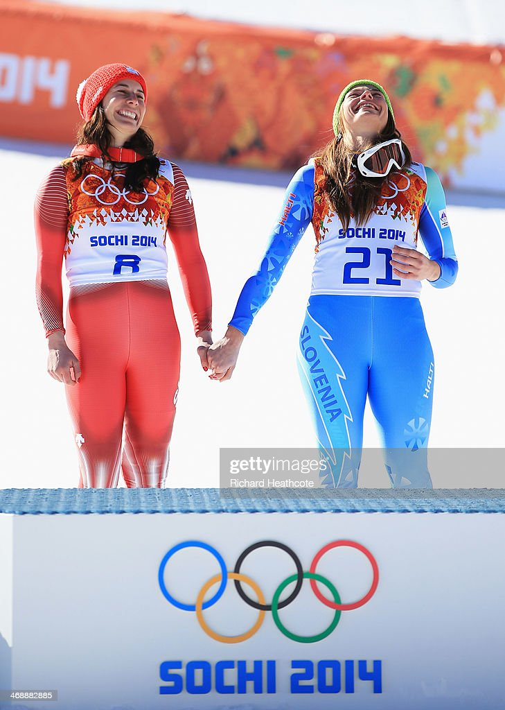 Gold medalists Dominique Gisin of Switzerland and Tina Maze of Slovenia hold hands during the flower ceremony for during the Alpine Skiing Women's...