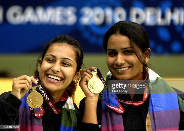 Gold medalists Heena Sidhu and Annu Raj Singh of India pose after the medal ceremony for the women's pairs 10 m air pistol event of the XIX...