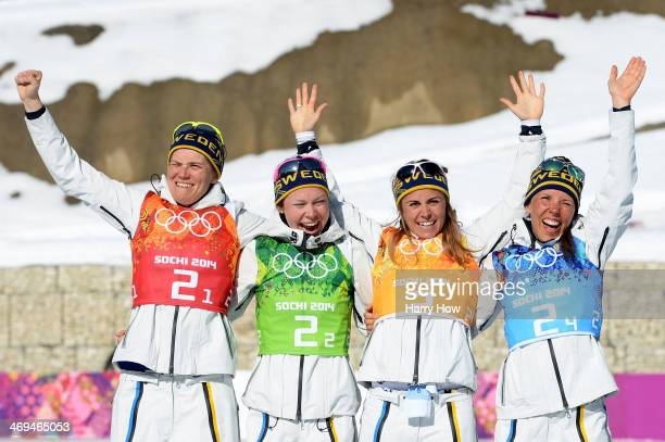Gold medalists Ida Ingemarsdotter Emma Wiken Anna Haag and Charlotte Kalla of Sweden celebrate on the podium during the flower ceremony for the...