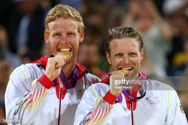 Gold medalists Jonas Reckermann and Julius Brink of Germany celebrate with their medals during the medal ceremony for the Men's Beach Volleyball on...