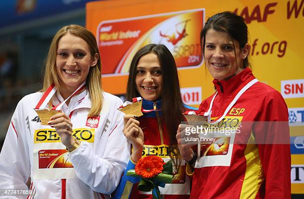 Gold medalists Kamila Licwinko of Poland and Maria Kuchina of Russia pose with bronze medalist Ruth Beitia of Spain during the medal ceremony for the...