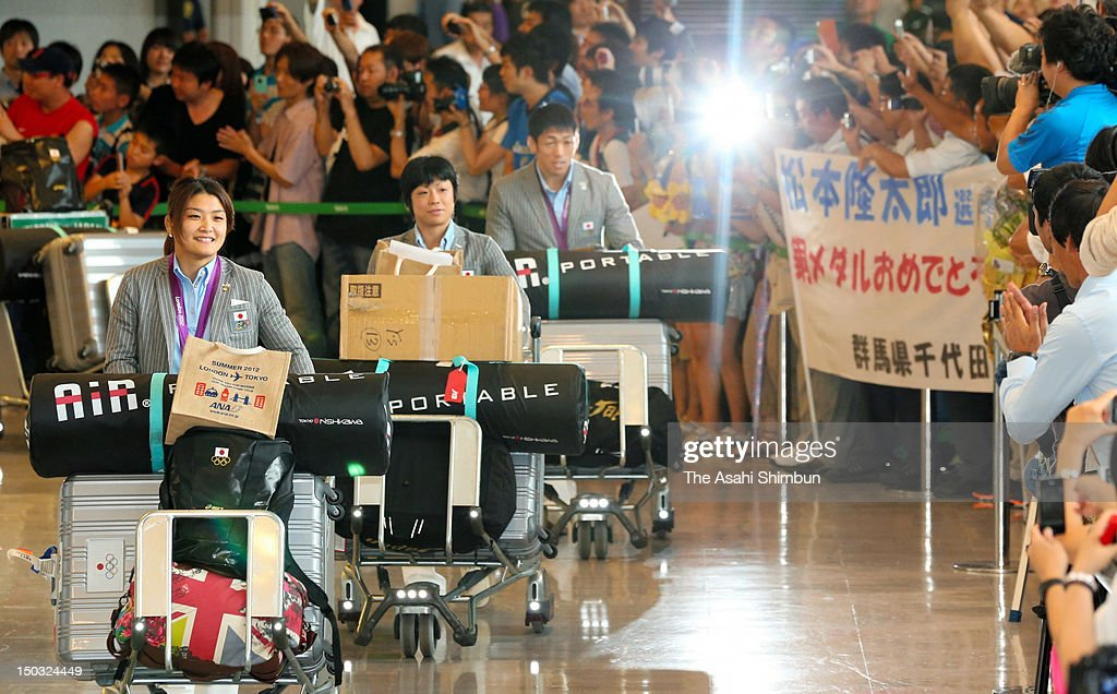Gold medalists Kaori Icho Hitomi Obara and Tatsuhiro Yomenitsu are welcomed upon arrival at Narita International Airport on August 14 2012 in Narita...