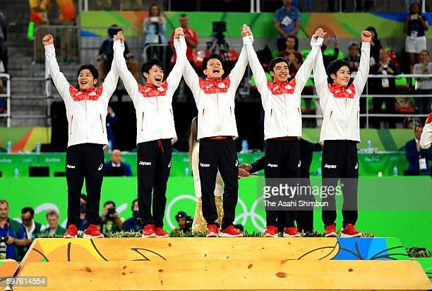 Gold medalists Koji Yamamuro Kohei Uchimura Yusuke Tanaka Kenzo Shirai and Ryohei Kato of Japan celebrate on the podium at the medal ceremony for the...