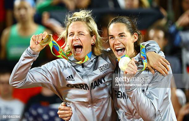 Gold medalists Laura Ludwig and Kira Walkenhorst of Germany celebrate on the podium during the medal ceremony for the Women's Beach Volleyball on day...