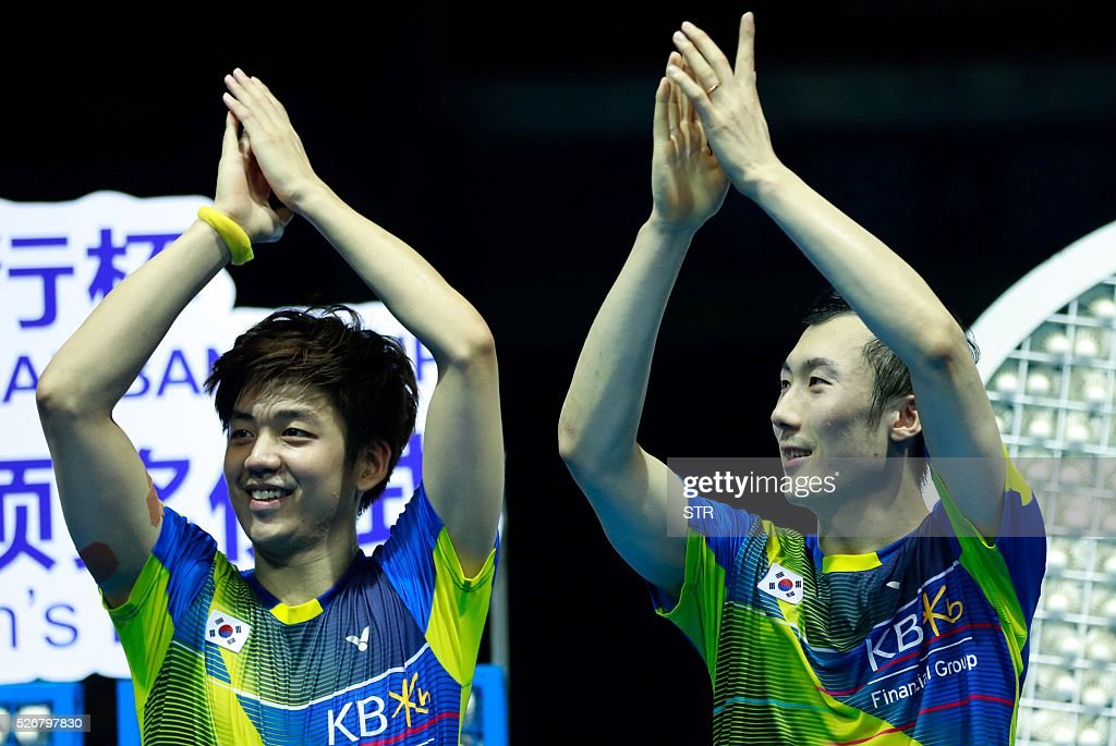 Gold medalists Lee Yong Dae (L) and Yoo Yeon Seong of South Korea attend the award ceremony of the men's doubles final at the 2016 Badminton Asia Championships in Wuhan, central China's Hubei province on May 1, 2016. / AFP / STR