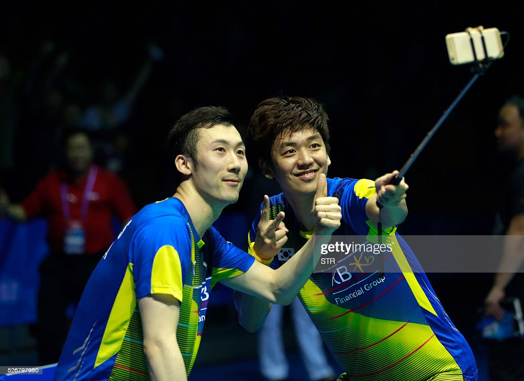 Gold medalists Lee Yong Dae (R) and Yoo Yeon Seong of South Korea use a selfie stick to take photos with fans after winning the men's doubles final match against Li Junhui and Liu Yuchen of China at the 2016 Badminton Asia Championships in Wuhan, central China's Hubei province on May 1, 2016. / AFP / STR