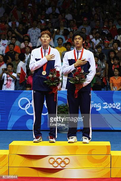 Gold medalists Lee Yongdae and Lee Hyojung of South Korea are pistured during their national anthem after winning the Mixed Doubles Gold Medal Match...