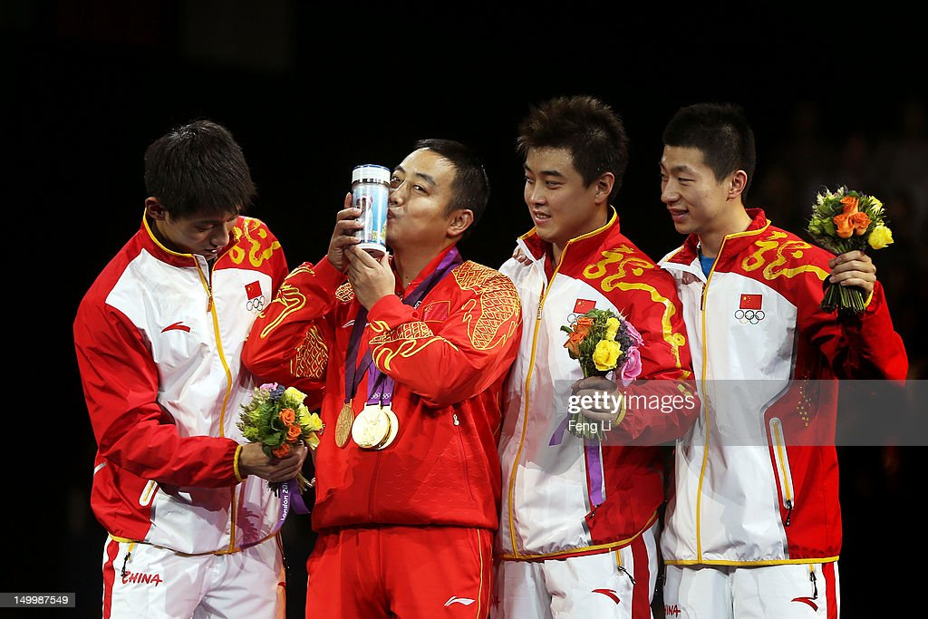 Gold medalists <a gi-track='captionPersonalityLinkClicked' href=/galleries/search?phrase=Ma+Long&family=editorial&specificpeople=2158981 ng-click='$event.stopPropagation()'>Ma Long</a> (L), Wang Hao (2nd R) and <a gi-track='captionPersonalityLinkClicked' href=/galleries/search?phrase=Zhang+Jike&family=editorial&specificpeople=4979400 ng-click='$event.stopPropagation()'>Zhang Jike</a> (R) celebrate with their coach <a gi-track='captionPersonalityLinkClicked' href=/galleries/search?phrase=Liu+Guoliang&family=editorial&specificpeople=655363 ng-click='$event.stopPropagation()'>Liu Guoliang</a> (2nd L) of China after putting their medals around his neck during the medal ceremony for the Men's Team Table Tennis on Day 12 of the London 2012 Olympic Games at ExCeL on August 8, 2012 in London, England.