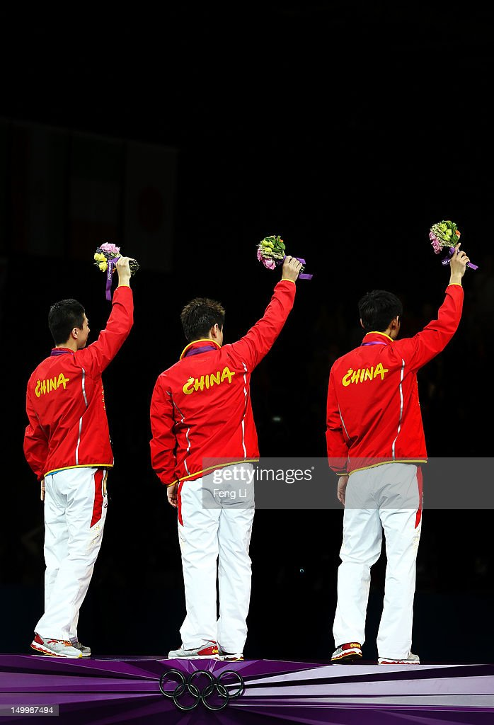 Gold medalists Ma Long (R), Wang Hao (C) and Zhang Jike (L) of China celebrate on the podium during the medal ceremony for the Men's Team Table Tennis on Day 12 of the London 2012 Olympic Games at ExCeL on August 8, 2012 in London, England.
