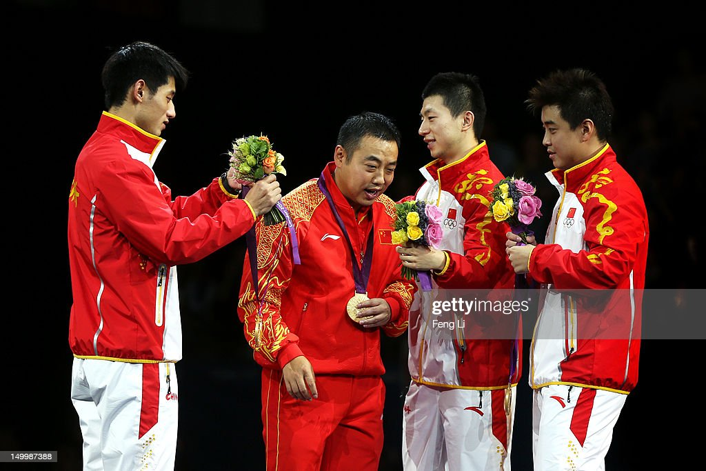 Gold medalists Ma Long (2nd R), Wang Hao (R) and Zhang Jike of China (L) celebrate with their coach Liu Guoliang (2nd L) by putting their medals around his neck during the medal ceremony for the Men's Team Table Tennis on Day 12 of the London 2012 Olympic Games at ExCeL on August 8, 2012 in London, England.