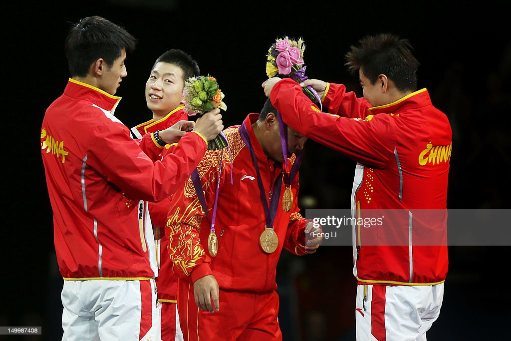 Gold medalists Ma Long (2nd L), Wang Hao (R) and Zhang Jike of China(L) celebrate with their coach Liu Guoliang (2nd R) by putting their medals around his neck during the medal ceremony for the Men's Team Table Tennis on Day 12 of the London 2012 Olympic Games at ExCeL on August 8, 2012 in London, England.