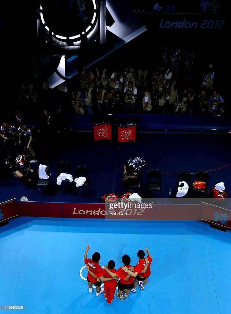 Gold medalists <a gi-track='captionPersonalityLinkClicked' href=/galleries/search?phrase=Ma+Long&family=editorial&specificpeople=2158981 ng-click='$event.stopPropagation()'>Ma Long</a> (R), Wang Hao (2nd R) and <a gi-track='captionPersonalityLinkClicked' href=/galleries/search?phrase=Zhang+Jike&family=editorial&specificpeople=4979400 ng-click='$event.stopPropagation()'>Zhang Jike</a> (L) of China celebrate with their coach <a gi-track='captionPersonalityLinkClicked' href=/galleries/search?phrase=Liu+Guoliang&family=editorial&specificpeople=655363 ng-click='$event.stopPropagation()'>Liu Guoliang</a> (2nd L) on the podium during the medal ceremony for the Men's Team Table Tennis on Day 12 of the London 2012 Olympic Games at ExCeL on August 8, 2012 in London, England.