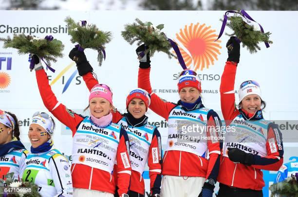 Gold medalists Maiken Caspersen Falla Heidi Weng Astrid Uhrenholdt Jacobsen and Marit Bjoergen of Norway celebrate during the flower ceremony for the...