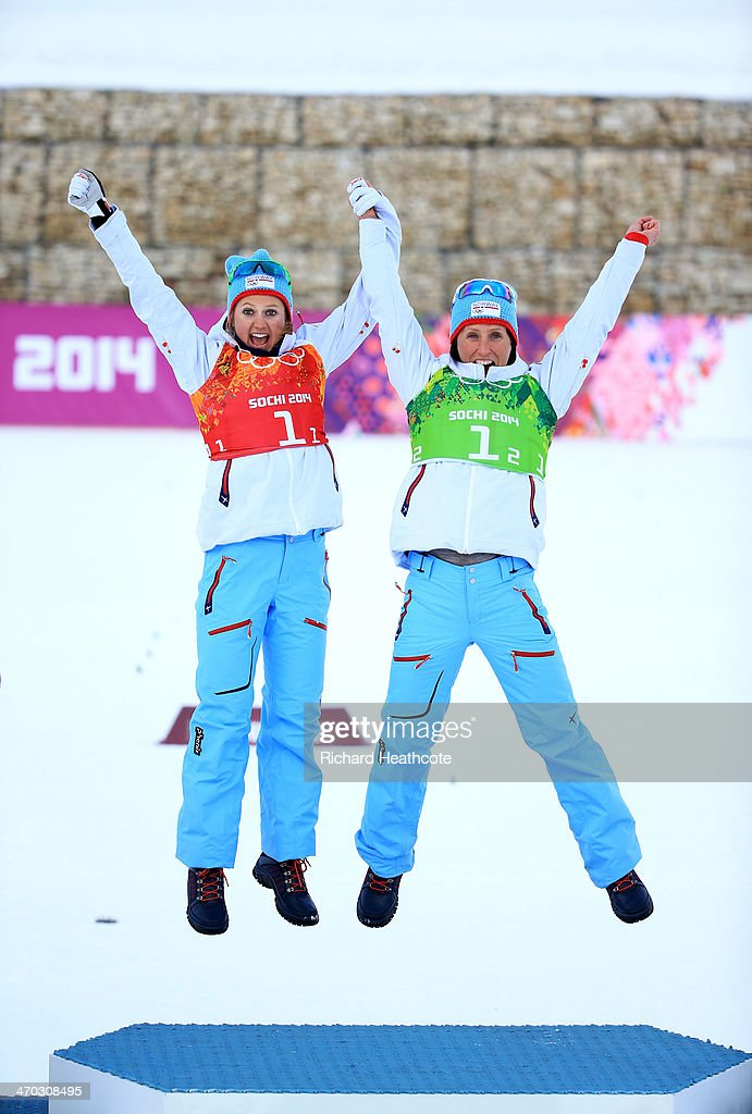 Gold medalists Marit Bjoergen (R) of Norway and <a gi-track='captionPersonalityLinkClicked' href=/galleries/search?phrase=Ingvild+Flugstad+Oestberg&family=editorial&specificpeople=7427144 ng-click='$event.stopPropagation()'>Ingvild Flugstad Oestberg</a> of Norway celebrate during the flower ceremony for the Women's Team Sprint Classic Final during day 12 of the 2014 Sochi Winter Olympics at Laura Cross-country Ski & Biathlon Center on February 19, 2014 in Sochi, Russia.