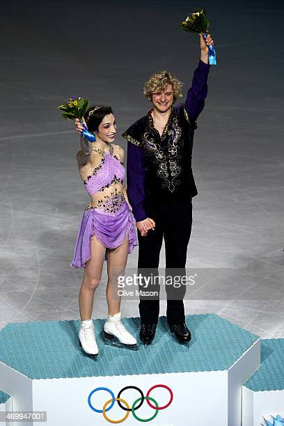 Gold medalists Meryl Davis and Charlie White of the United States celebrate on the podium during the flower ceremony for the Figure Skating Ice Dance...