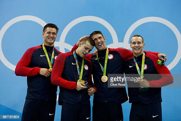 Gold medalists Nathan Adrian Ryan Held Michael Phelps and Caeleb Dressell of the United States pose on the podium during the medal ceremony for the...