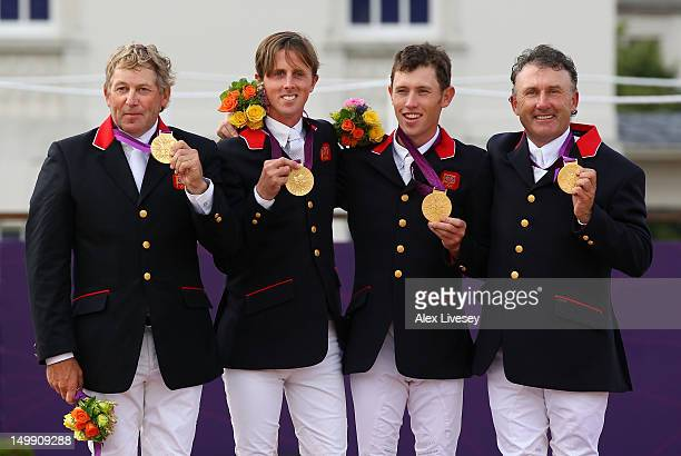 Gold medalists Nick Skelton Ben Maher Scott Brash and Peter Charles of Great Britain celebrate on the podium during the medal ceremony for the Team...