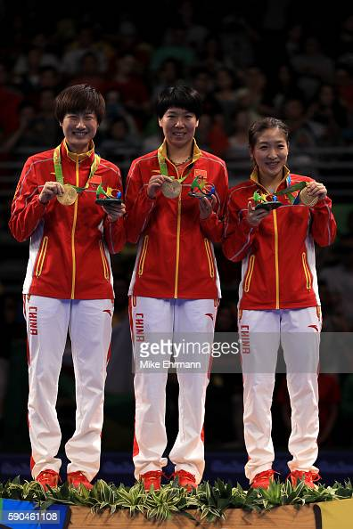 Gold medalists Ning Ding Xiaoxia Li and Shiwen Liu of China pose on the podium during the medal ceremony for the Women's Team Match between China and...
