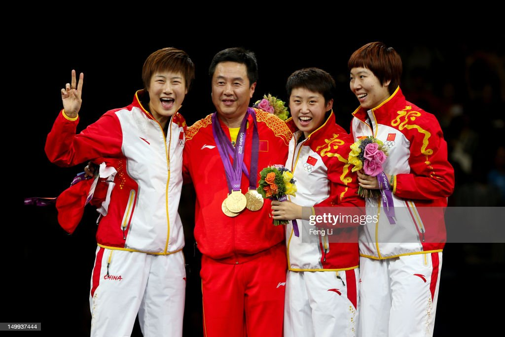 Gold medalists Ning Ding Yue Guo and Xiaoxia Li of China celebrate on the podium after putting their gold medals around the neck of head coach Shi...
