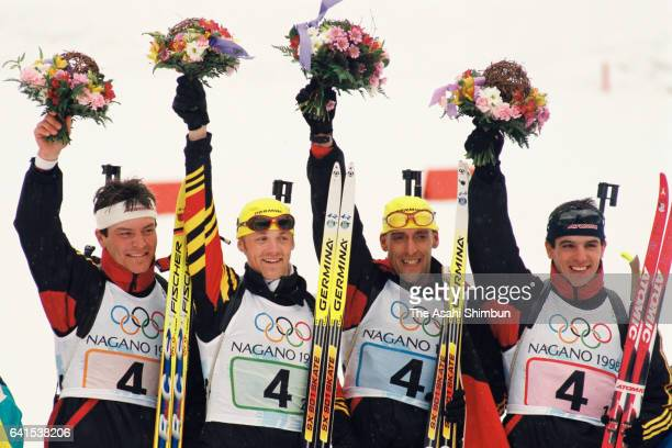 Gold medalists Ricco Gross Peter Sendel Sven Fischer and Frank Luck of Germany celebrate on the podium at the flower ceremony for the Biathlon Men's...