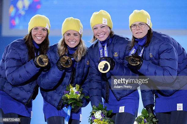Gold medalists Sweden celebrate on the podium during the medal ceremony for the Women's 4 x 5 km Relay on day 9 of the Sochi 2014 Winter Olympics at...