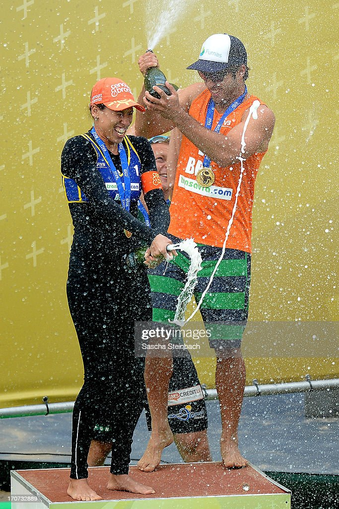 Gold medalists Taiana Lima (L) and Bruno Oscar Schmidt (R) of Brazil celebrate with champagne on the podium during the FIVB Grand Slam final match day at The Hague Beach Stadium on June 16, 2013 in The Hague, Netherlands.