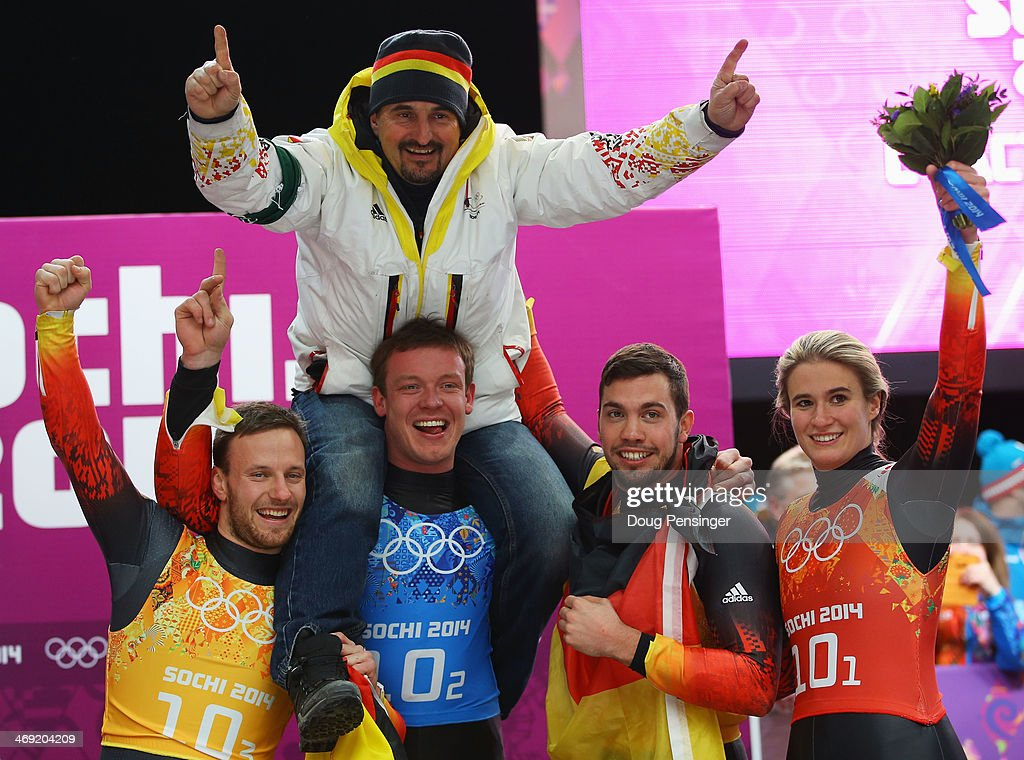 Gold medalists Tobias Arlt, Felix Loch, Tobias Wendl and Natalie Geisenberger of Germany lift their coach Georg Hackl in celebration during the flower ceremony for the the Luge Relay on Day 6 of the Sochi 2014 Winter Olympics at Sliding Center Sanki on February 13, 2014 in Sochi, Russia.