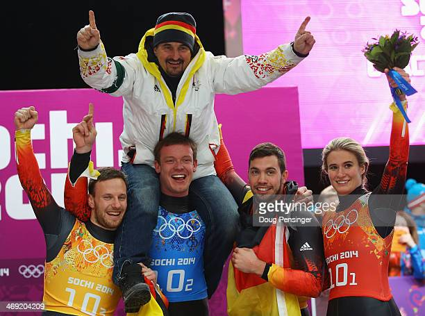 Gold medalists Tobias Arlt Felix Loch Tobias Wendl and Natalie Geisenberger of Germany lift their coach Georg Hackl in celebration during the flower...