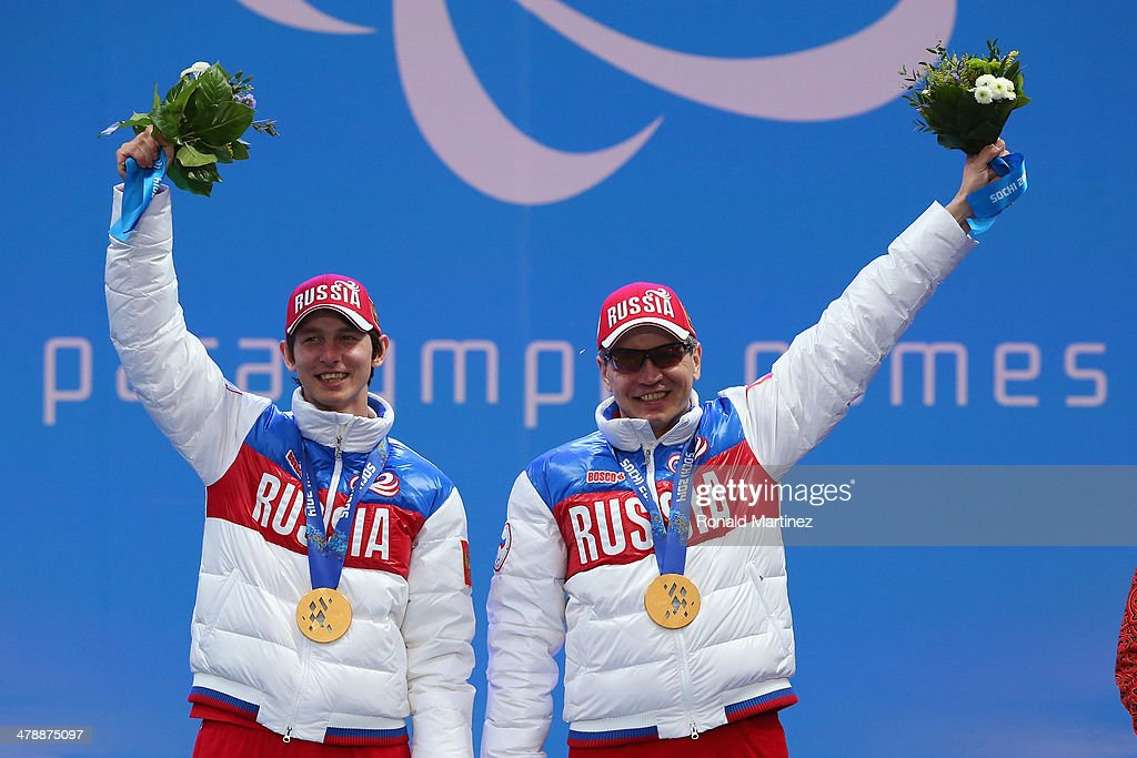 Gold medalists Valerii Redkozubov of Russia and guide Evgeny Geroev celebrate at the medal ceremony for men's Super Combined Visually Impaired on day eight of the Sochi 2014 Paralympic Winter Games at Laura Cross-country Ski & Biathlon Center on March 15, 2014 in Sochi, Russia.